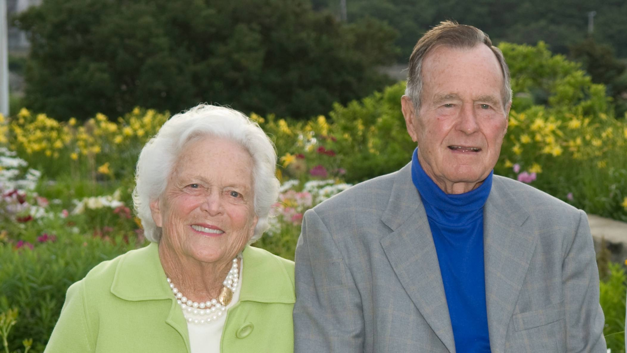 former President George Bush with his wife Barbara Bush sitting outside in a garden