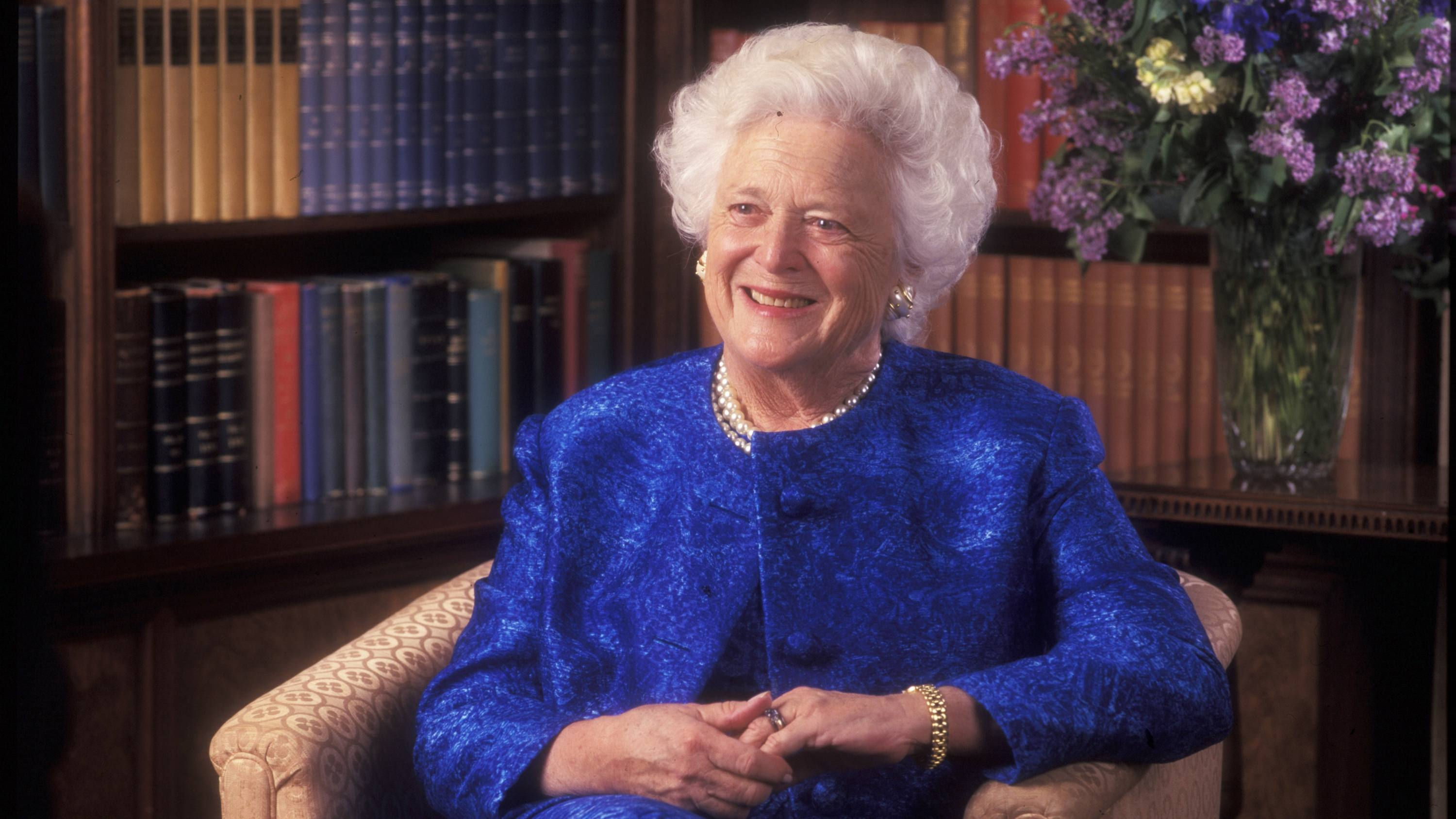 former First Lady Barbara Bush in a bright blue dress suit, sitting a library chair and smiling