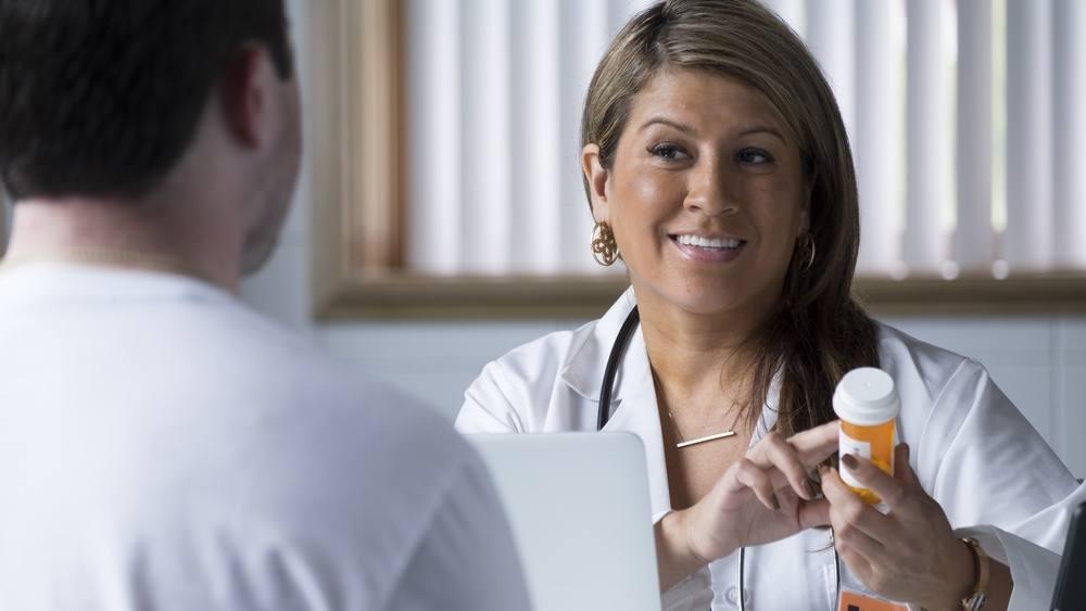 Una doctora habla con un paciente acerca del frasco de medicamentos