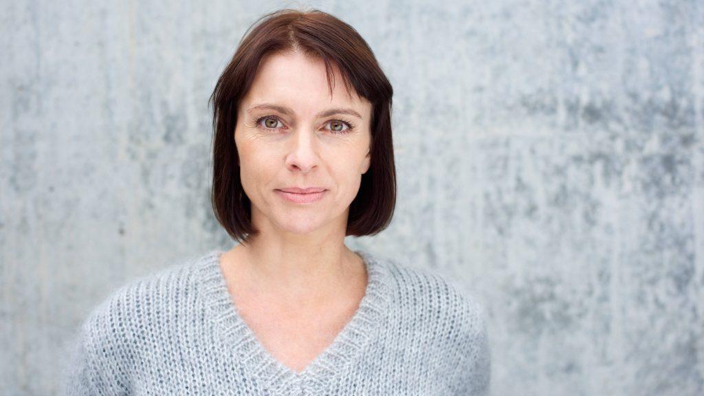 Foto de una mujer de mediana edad que mira seria a la cámara