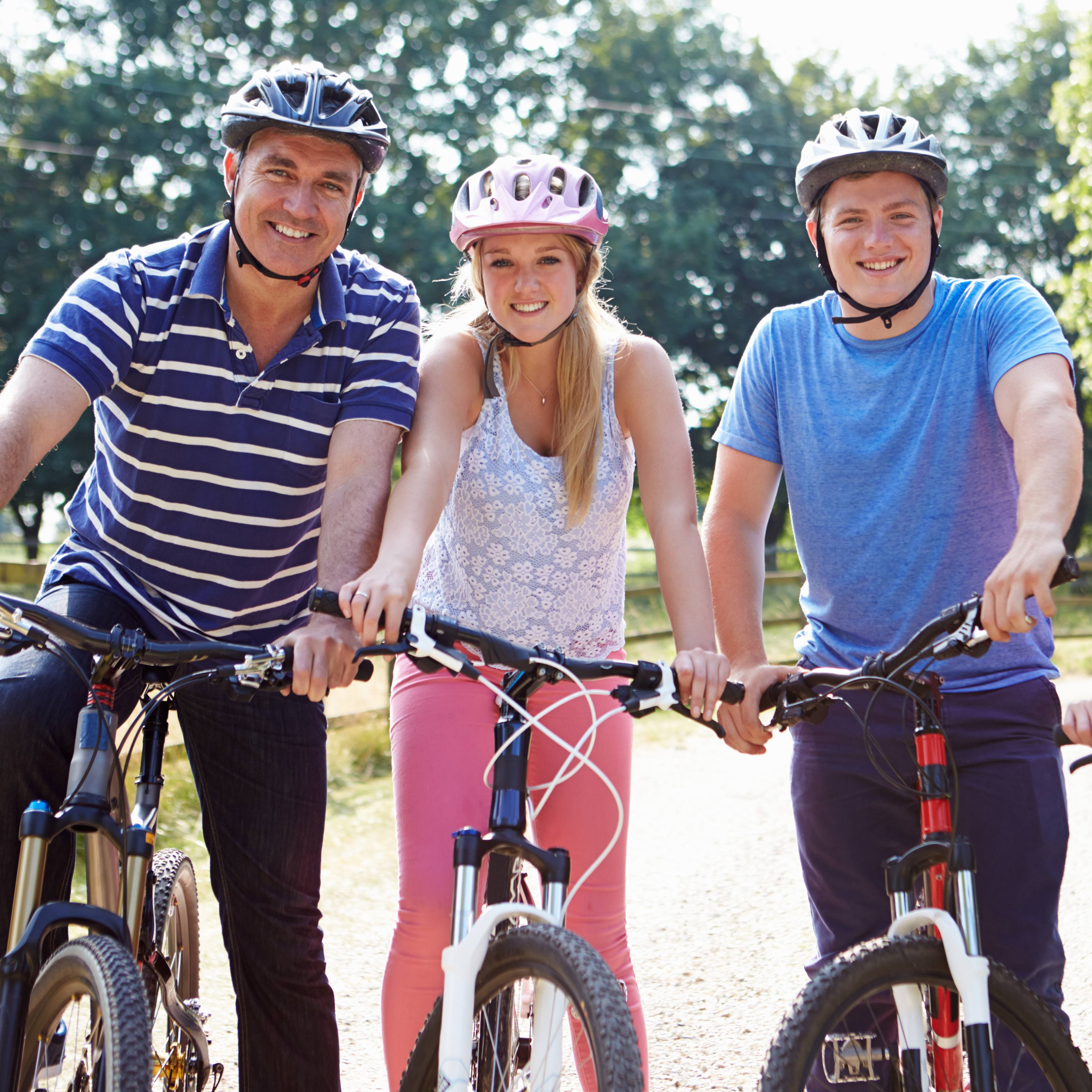 a family on bicycles - father and teenage daughter and son