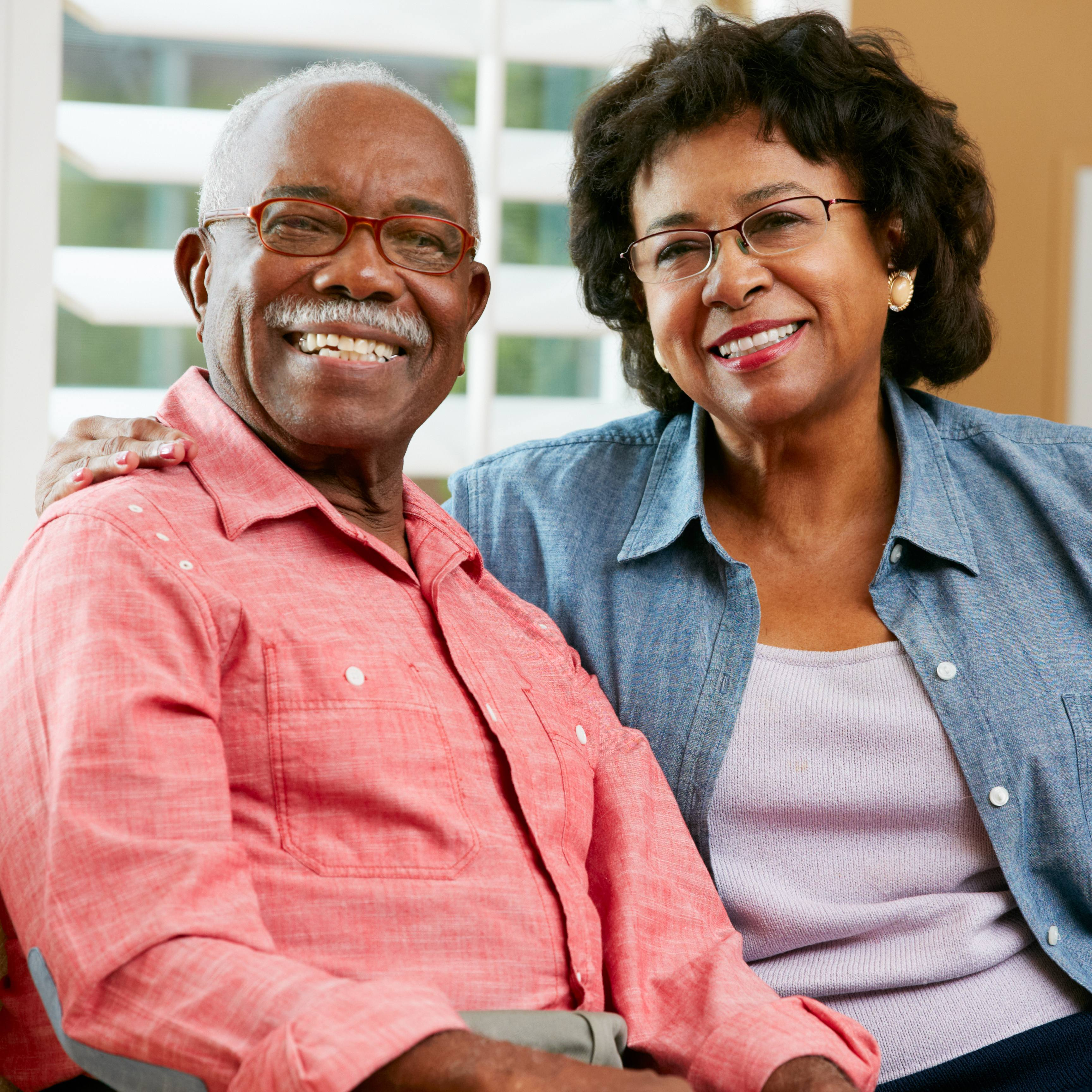 a smiling older couple at home, sitting together on a couch