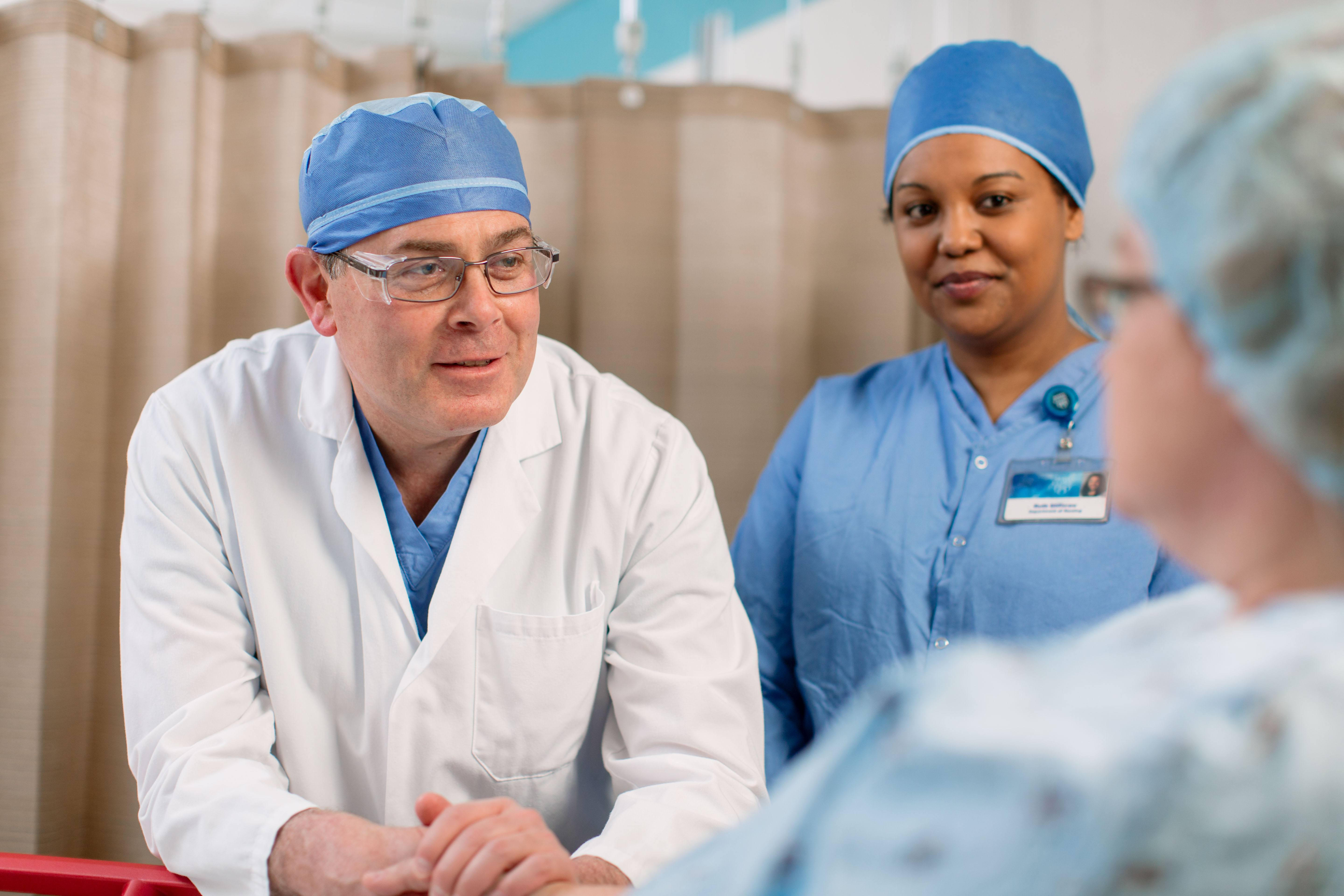 physician and nurse talking to patient