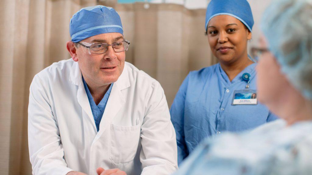 Un médico y una enfermera conversan con una paciente