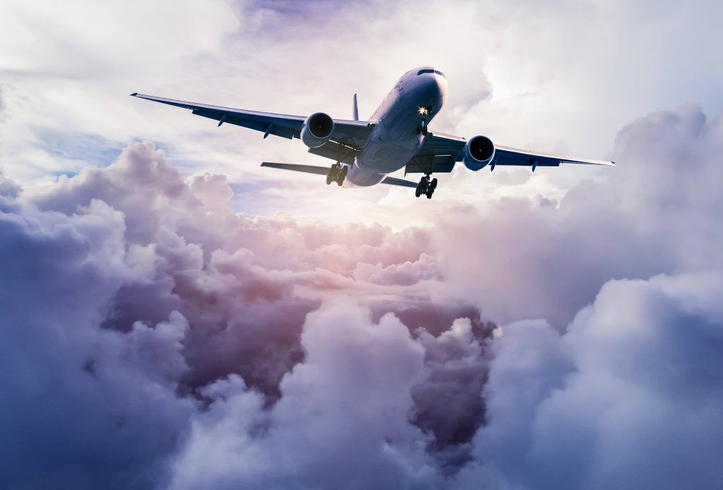 a large passenger jet airplane flying through the sky full of clouds