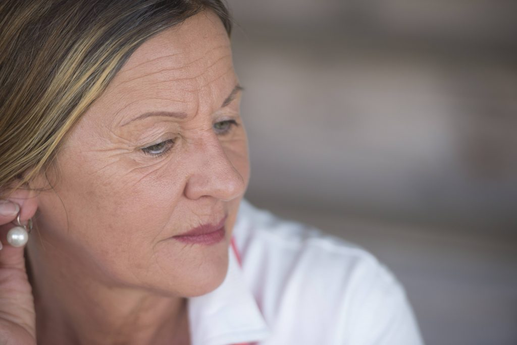 a close-up of an older woman looking worried, sad, tired, lonely, depressed