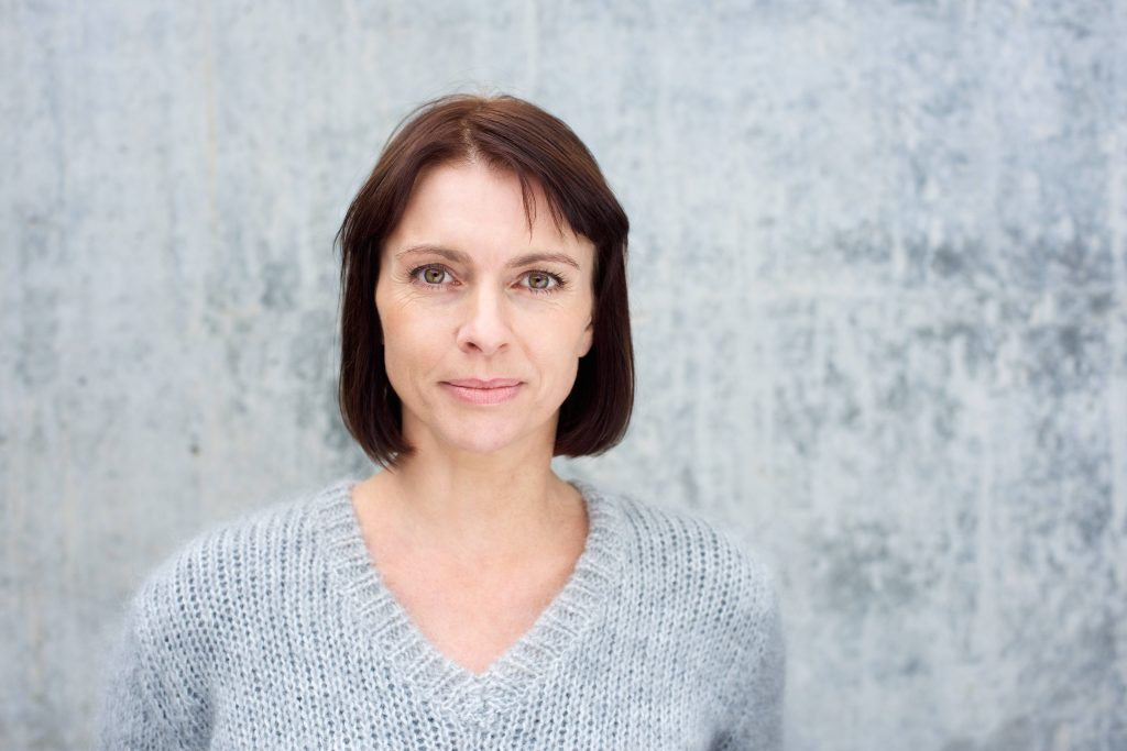 a close-up portrait of a serious-looking middle-aged woman, looking straight into the camera