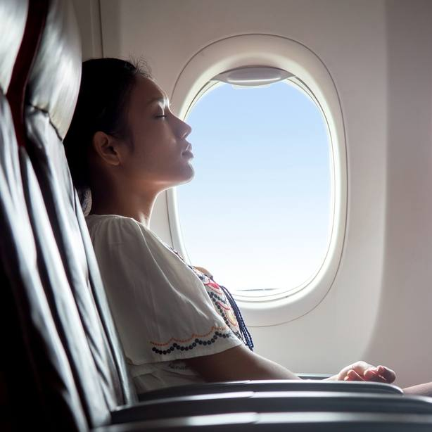 A young women sitting near a window on an airplane, with her eyes closed, resting or napping