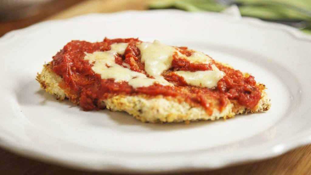 Mayo recipe of chicken Parmesan sprinkled with mozzarella cheese, on a white dinner plate