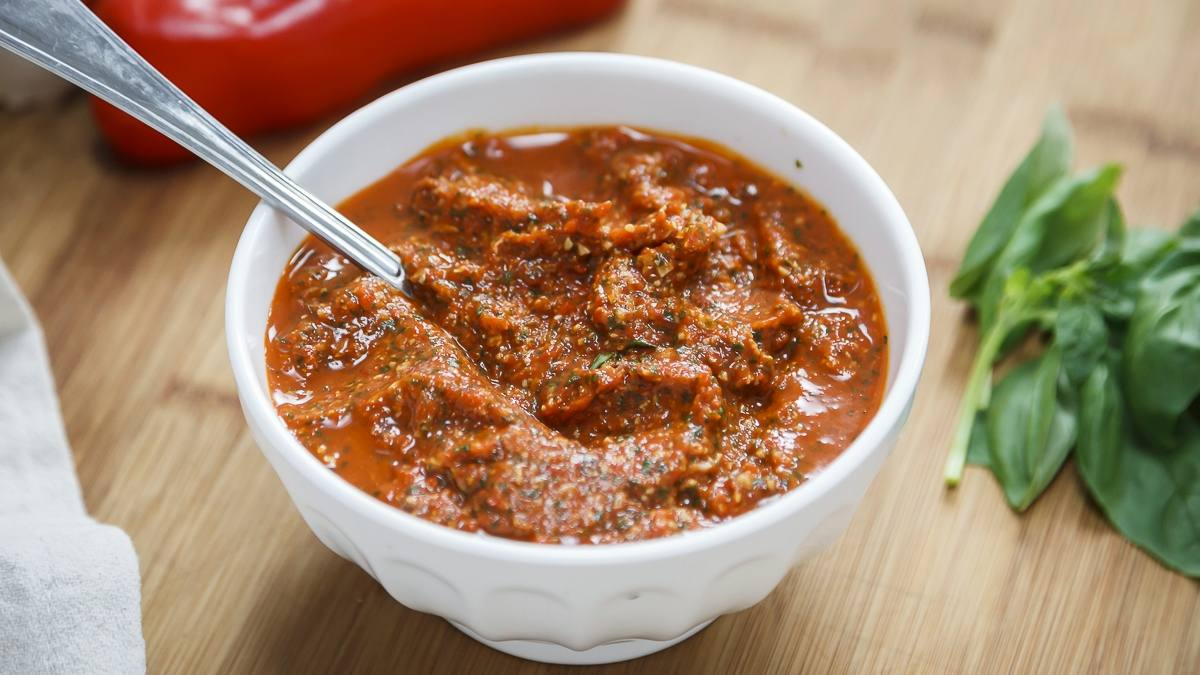 a white bowl of roasted red pepper pesto with a spoon in it