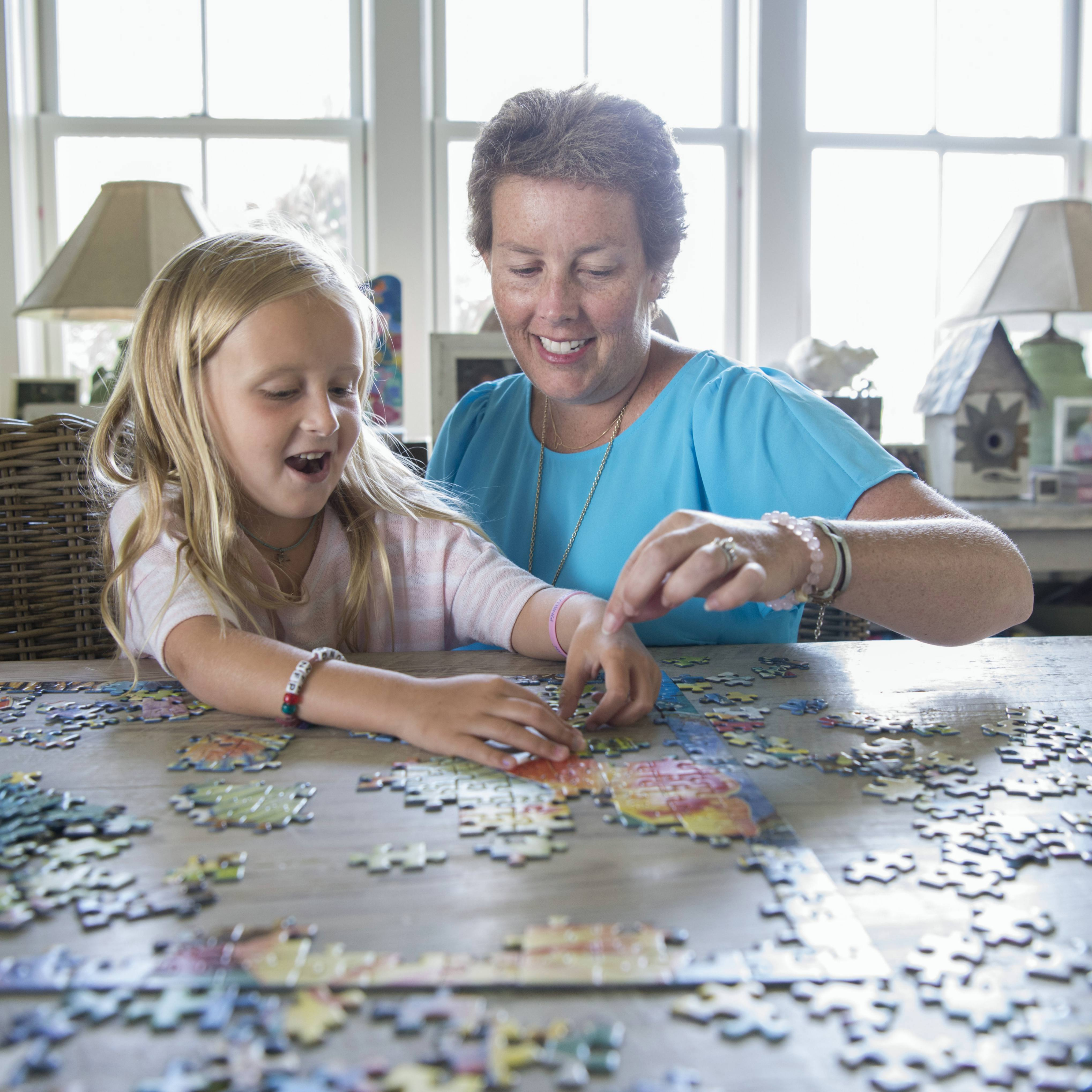 cancer patient Hollis Youngner working on a puzzle with her daughter