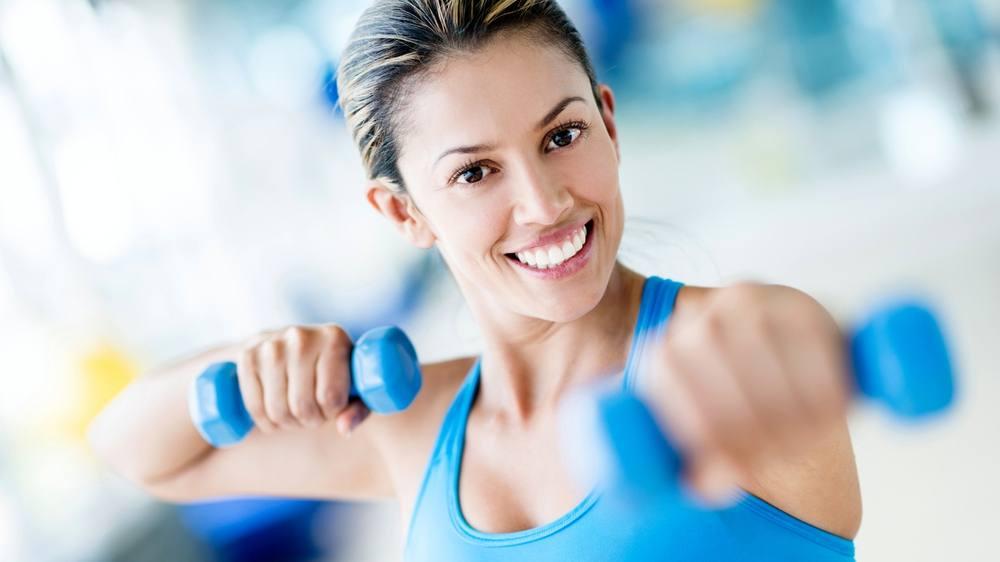 Una mujer fuerte levanta pesas en el gimnasio