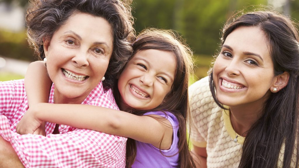 Acercamiento de tres generaciones: abuela, hija y nieta, quienes sonríen y se abrazan mientras están afuera