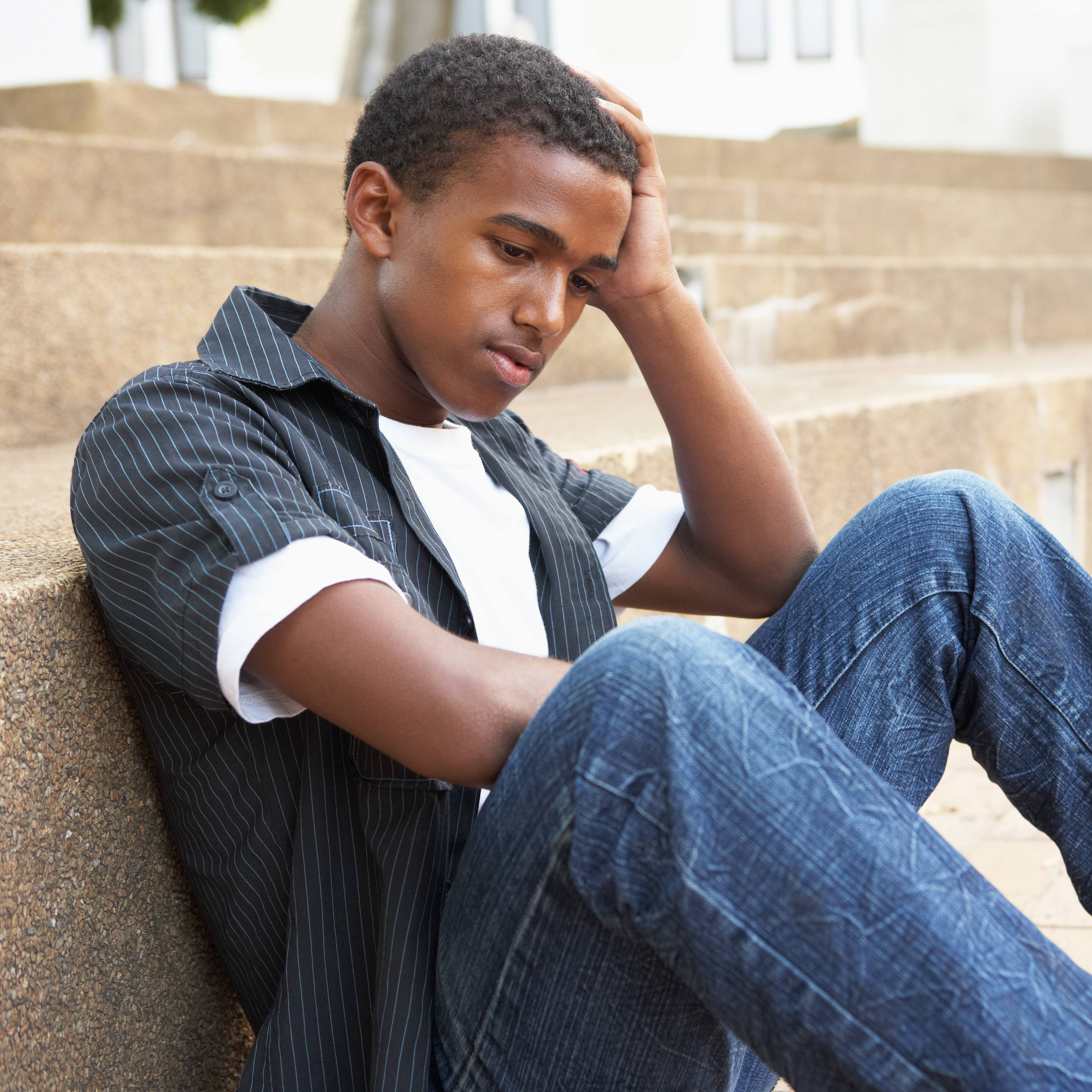 a teenage boy sitting on some steps with this head resting on his hand, looking sad or depressed