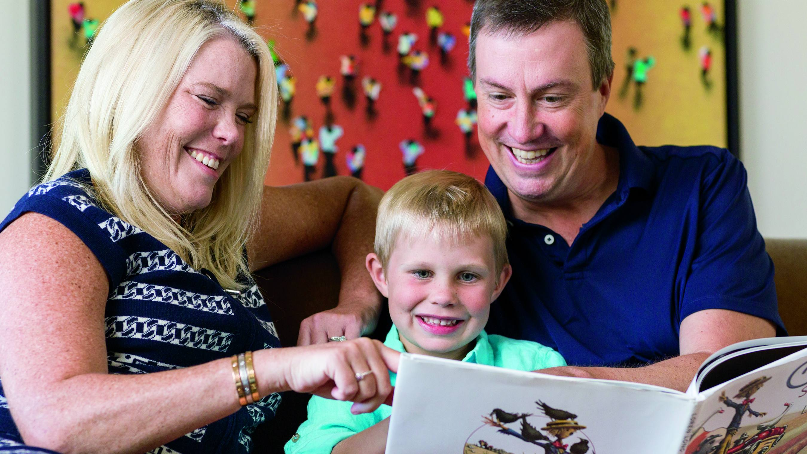 breast cancer patient Dawn Lenhardt smiling with her family and reading a children's book