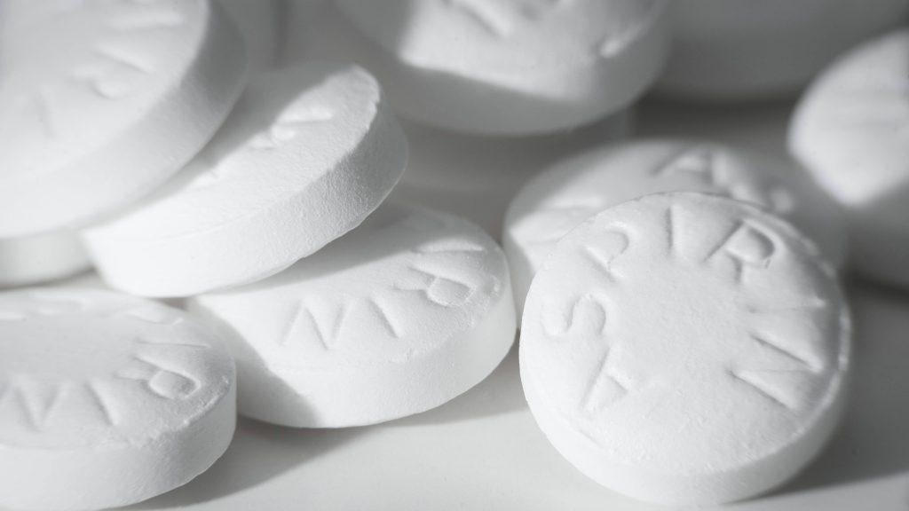 Varias tabletas de aspirina regadas sobre una superficie blanca