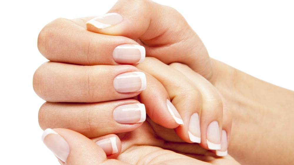 a closeup of a woman's hands and pretty (artificial) finger nails