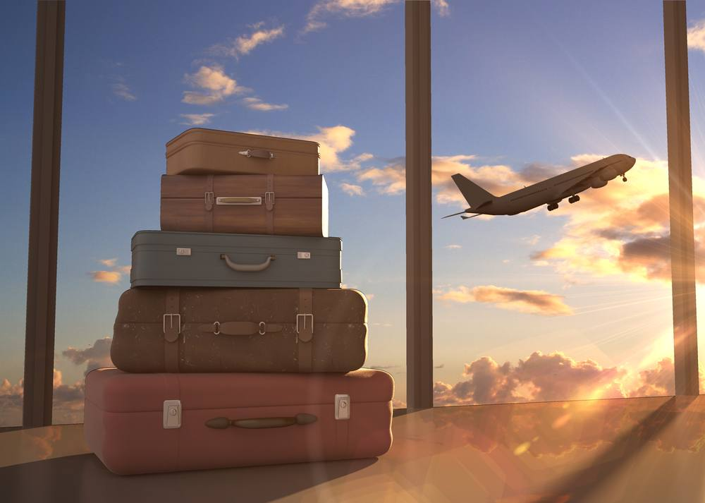 a stack of suitcases in front of large windows and a plane taking off into the sunset