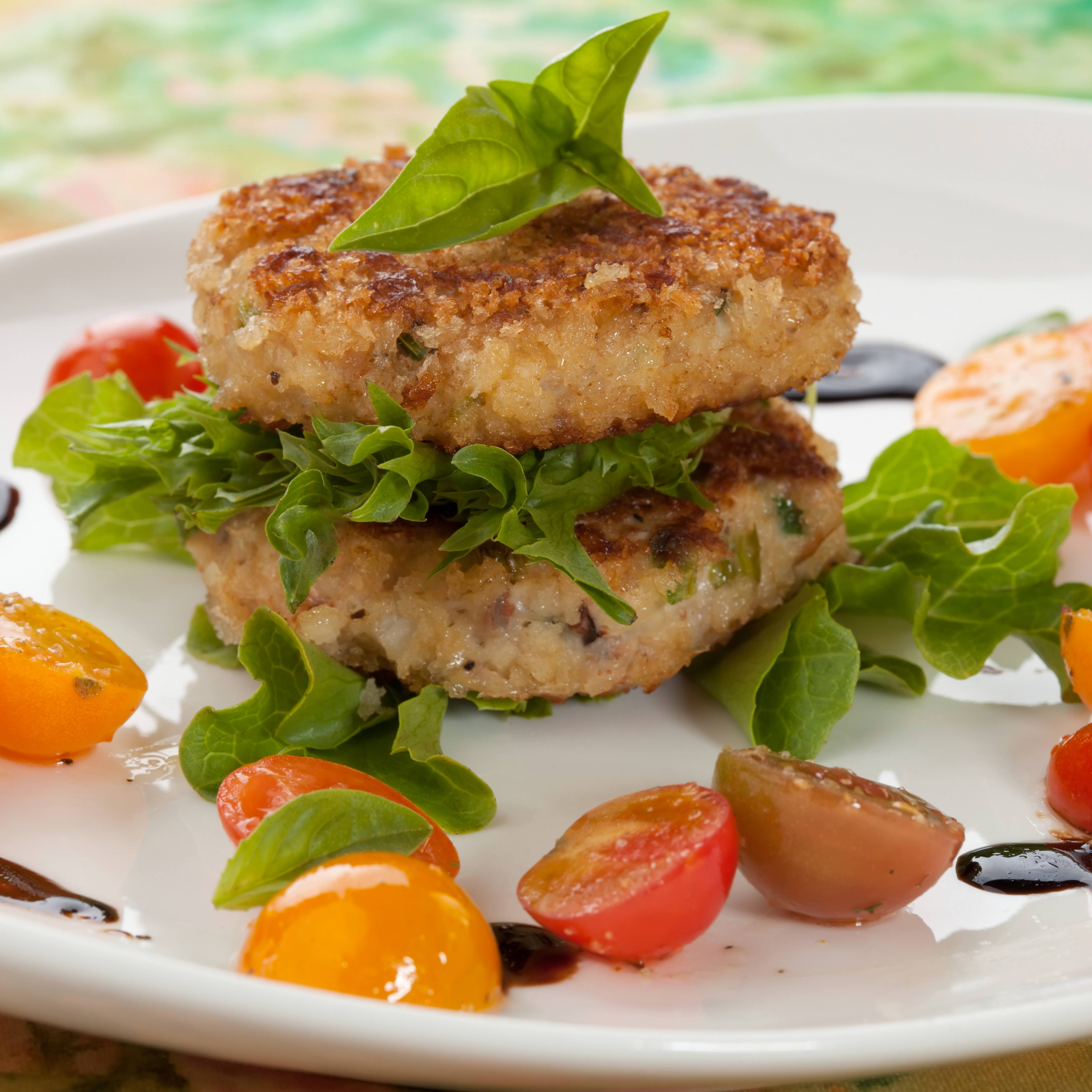 a plate with lettuce, tomatoes and crabcakes