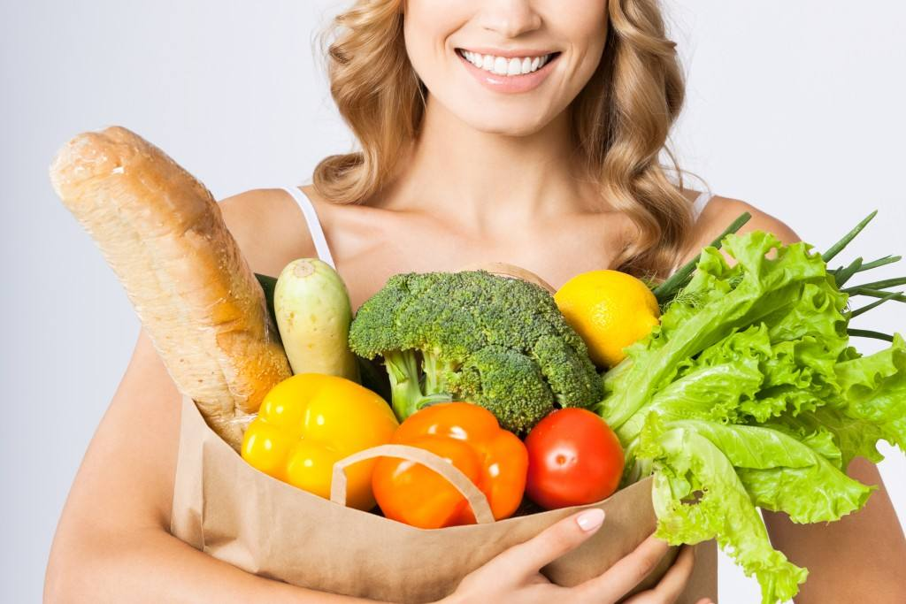 Woman holding grocery bag of vegetables, perhaps for a vegetarian diet