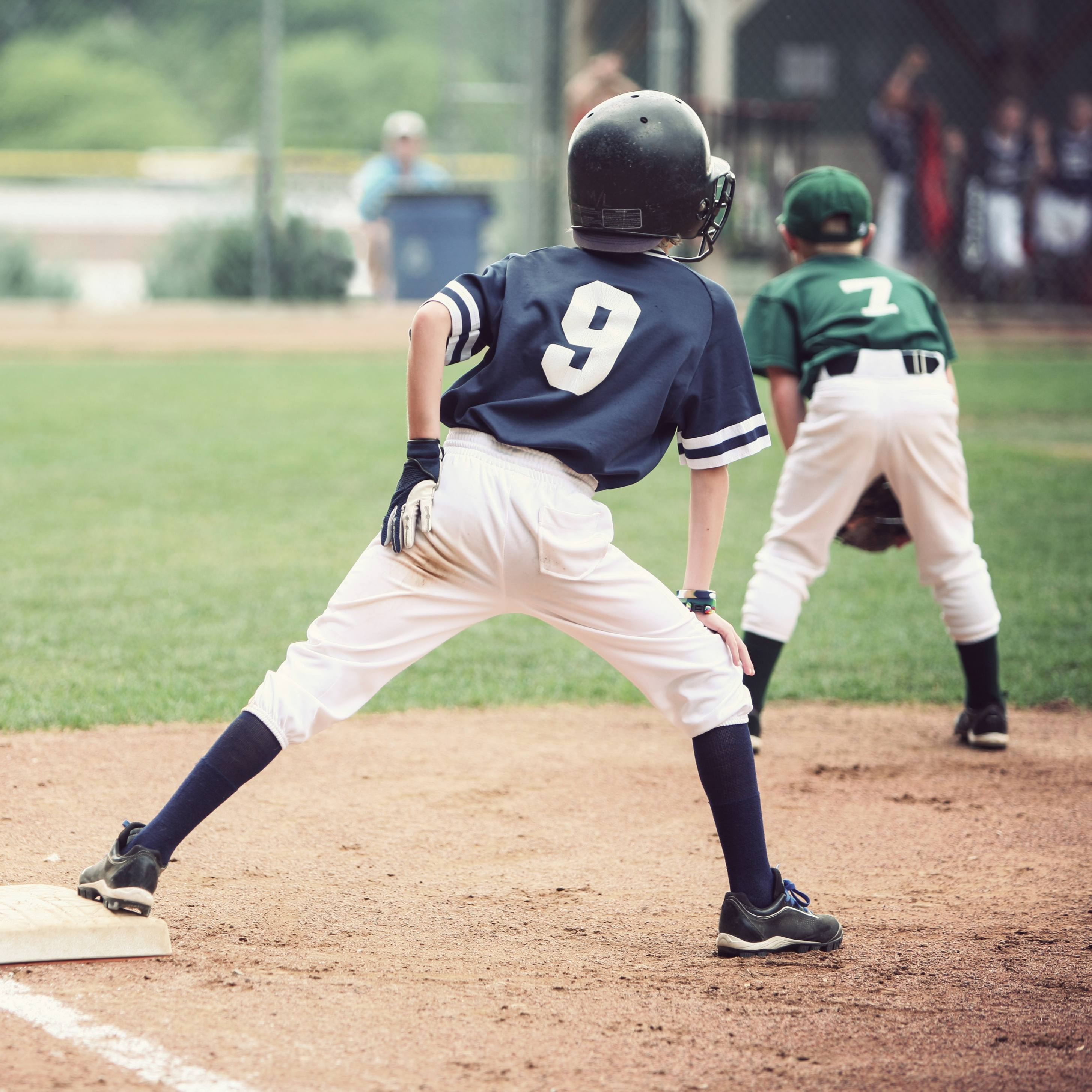 young baseball players on the field with one clinging to a base