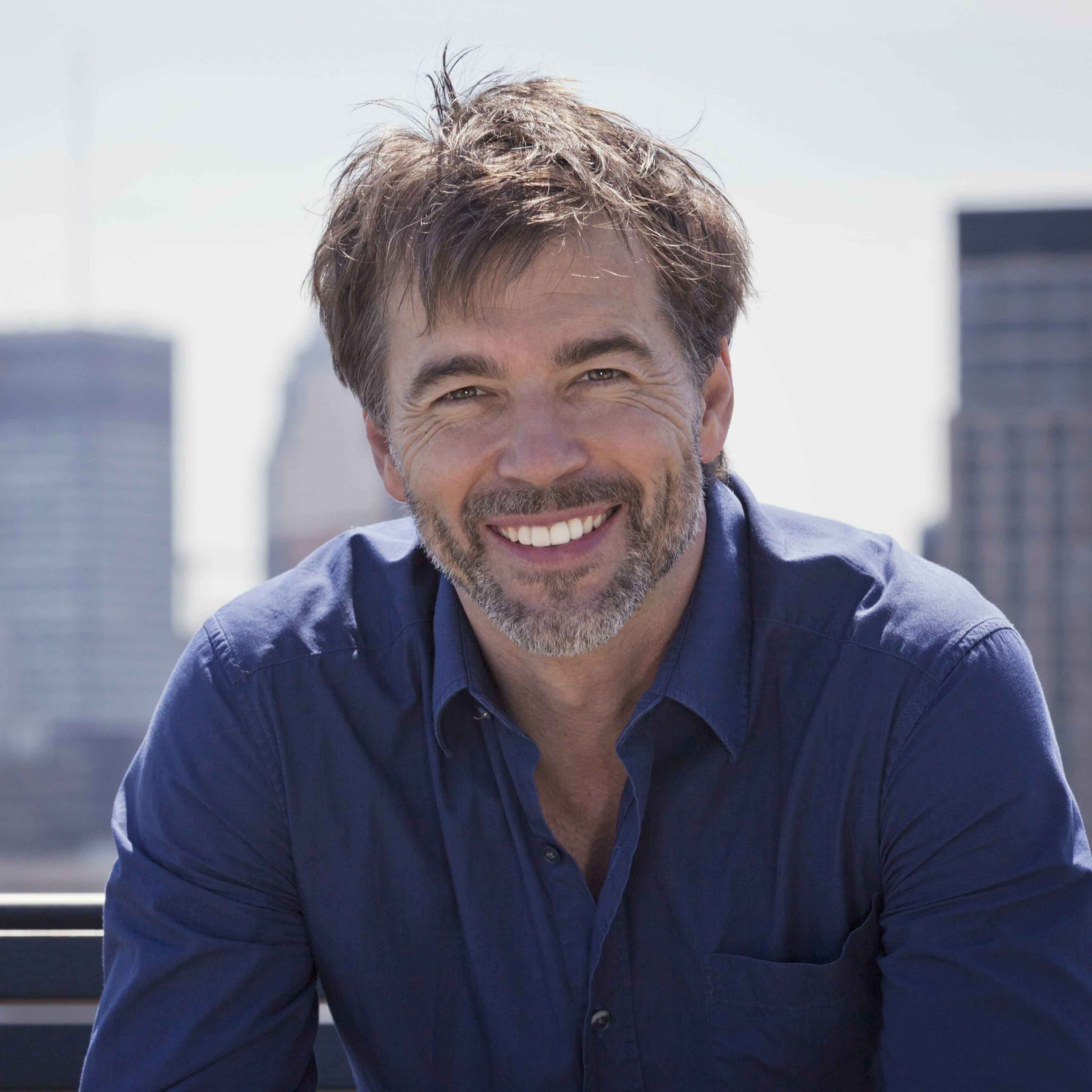 a happy and smiling middle-aged mature man outside with a city skyline in the background