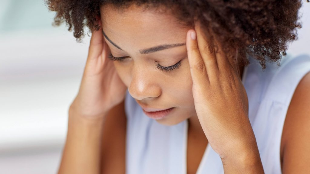 a young African American woman looking down and sad, holding her head because she has headache