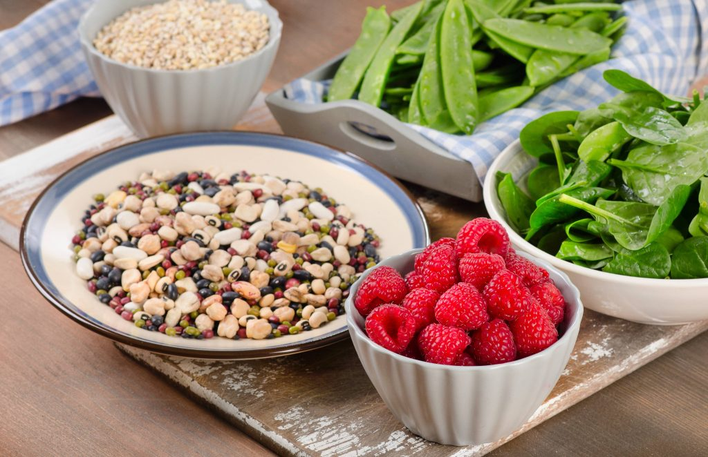 a selection of high-fiber foods - fruits, vegetables, whole grains and legumes - in assorted bowls on a wooden surface