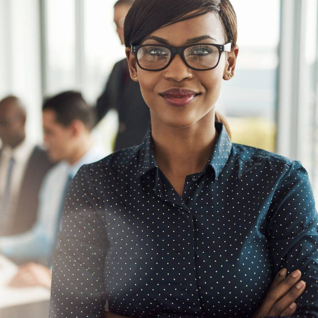 a young businesswoman wearng glasses and with her arms crossed, confident in an office setting