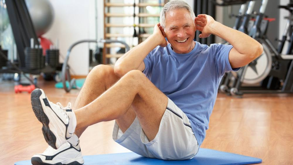 a middle-aged man in a gym on the flooring doing stretches and exercises