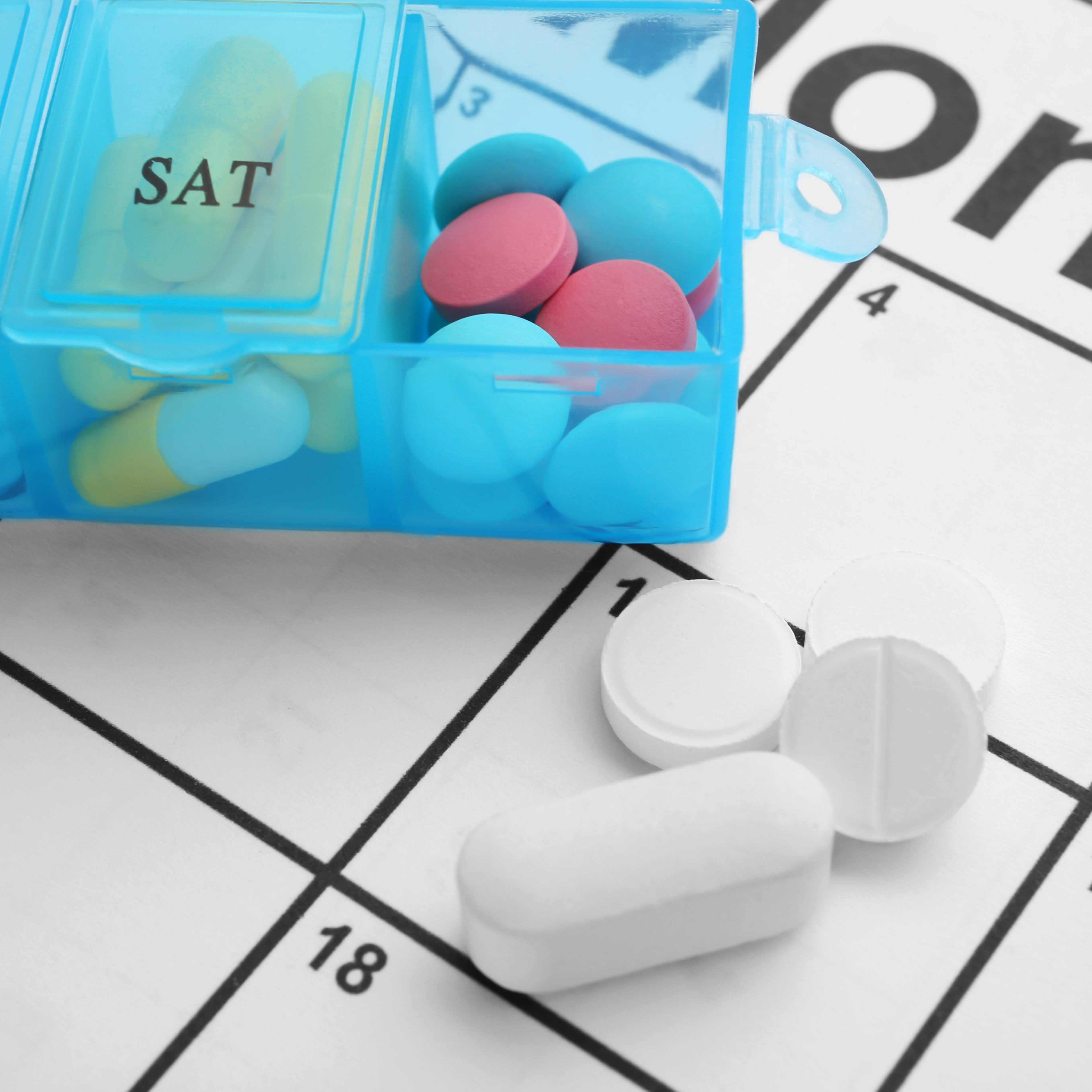 a pill box with different medicine tablets resting on a calendar