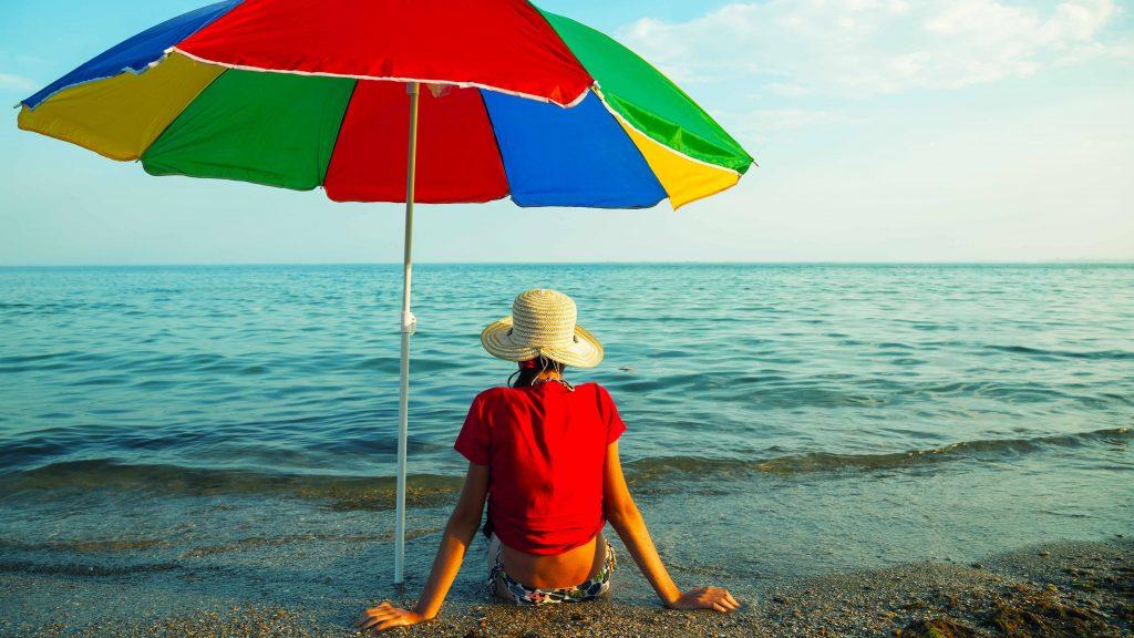 Una adolescente está sentada al sol en la playa, bajo una sombrilla y con un sombrero en la cabeza