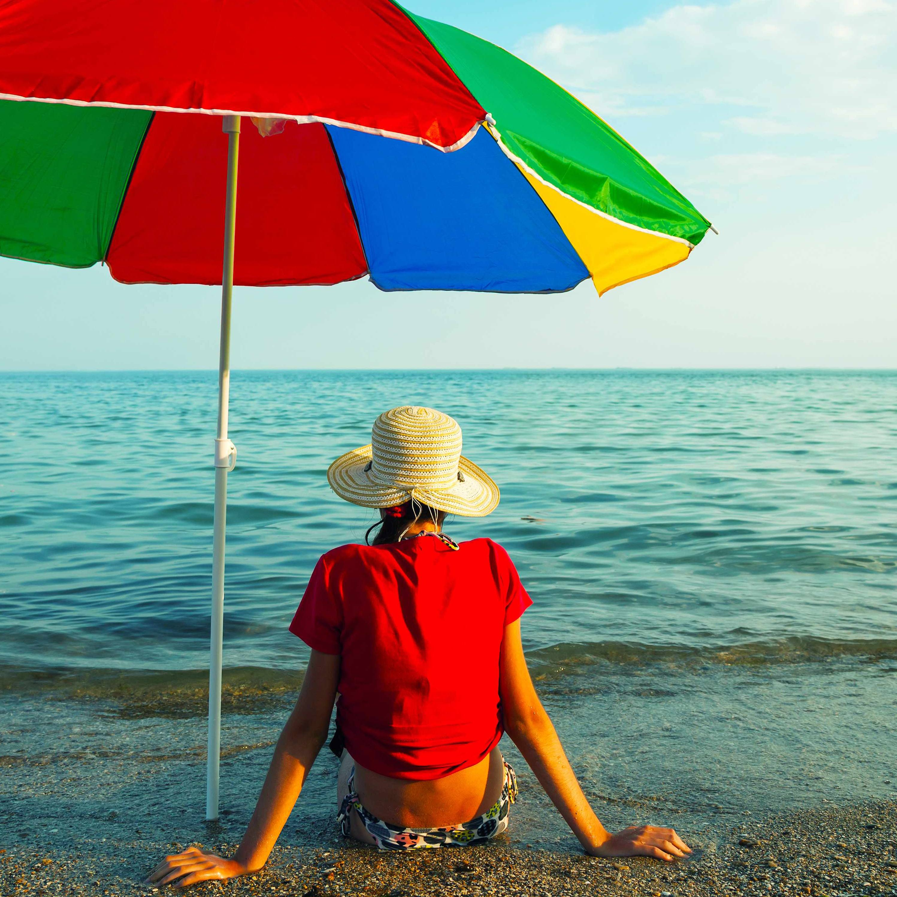 A young teen girl sitting in the sun under an umbrella on the beach with a hat on her head.