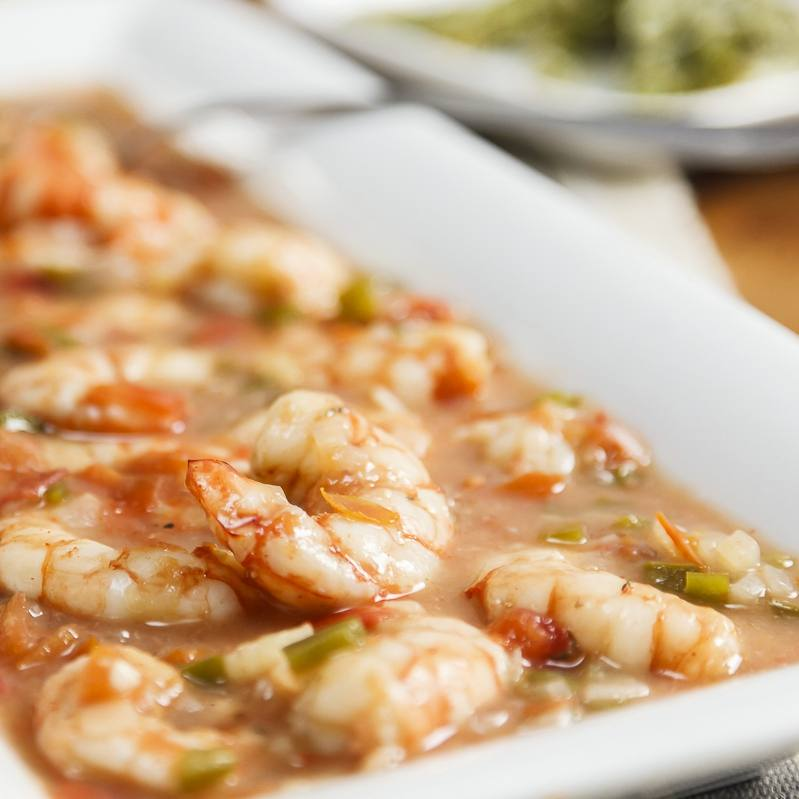 Spicy Creole shrimp dish on a white plate with rice and asparagus in the background