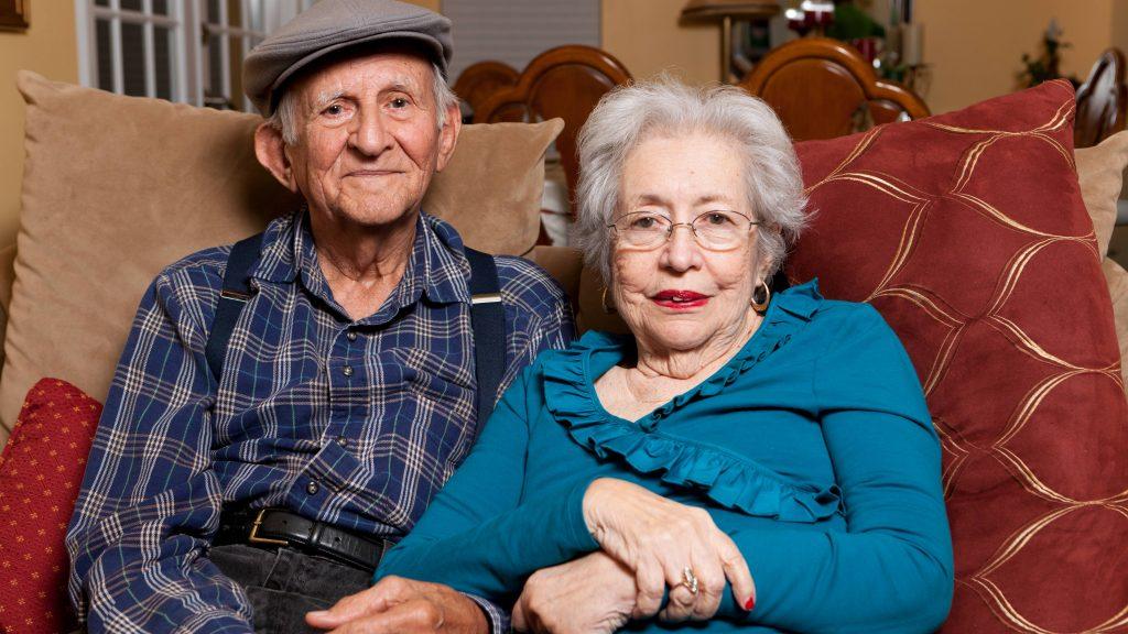 Una pareja de ancianos de más de 80 años sentados cariñosamente juntos en su casa