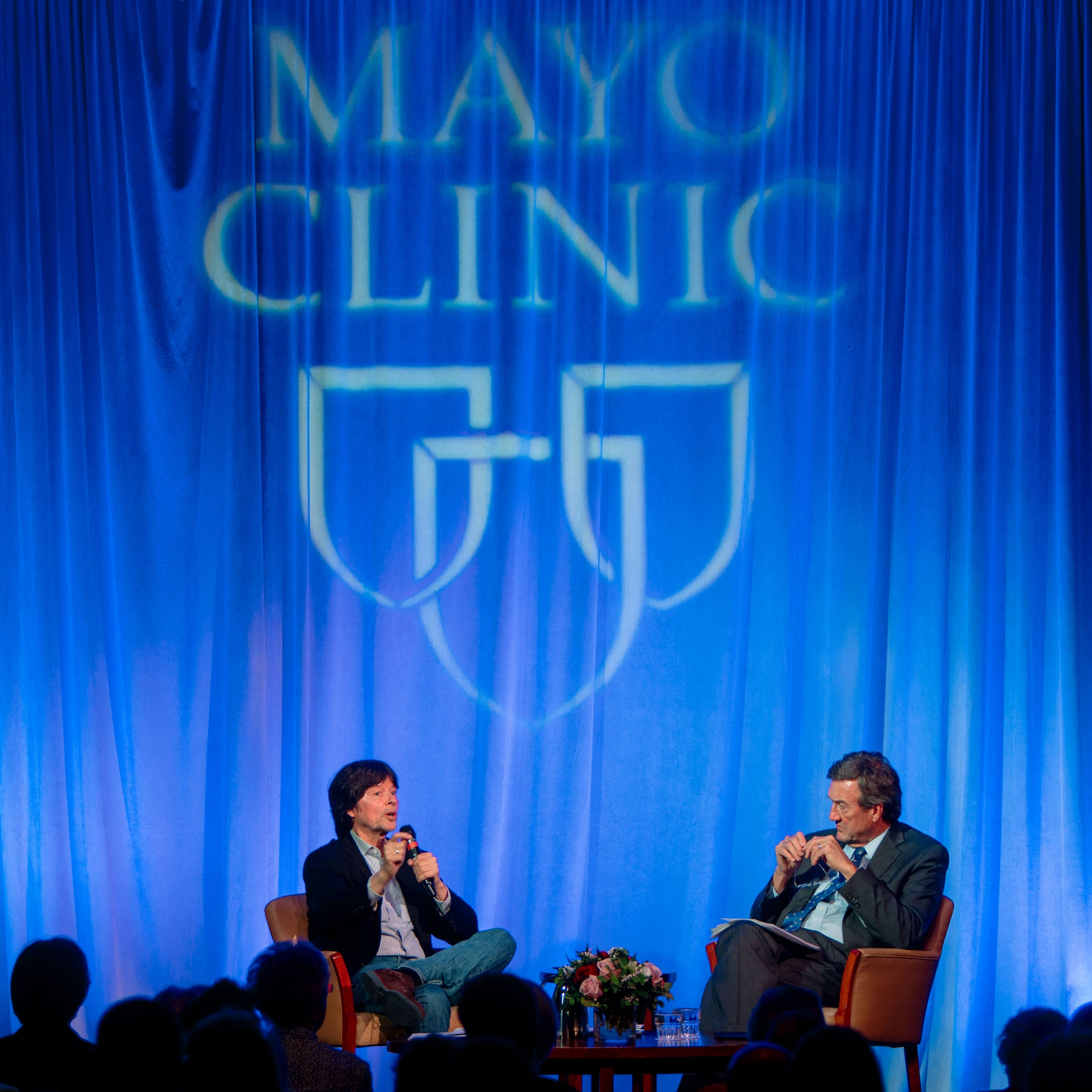 Photo of two males, Ken Burns and Dr. John Noseworthy on stage with a blue backdrop with the Mayo Clinic Logo of three shields