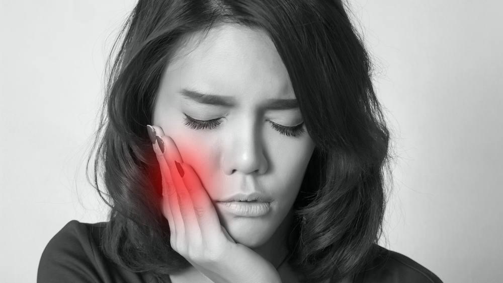 Una mujer joven presiona su mejilla con expresión de dolor porque tiene un dolor de muelas terrible.