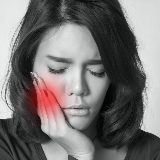 Young woman pressing her bruised cheek with a painful expression as if she's having a terrible toothache