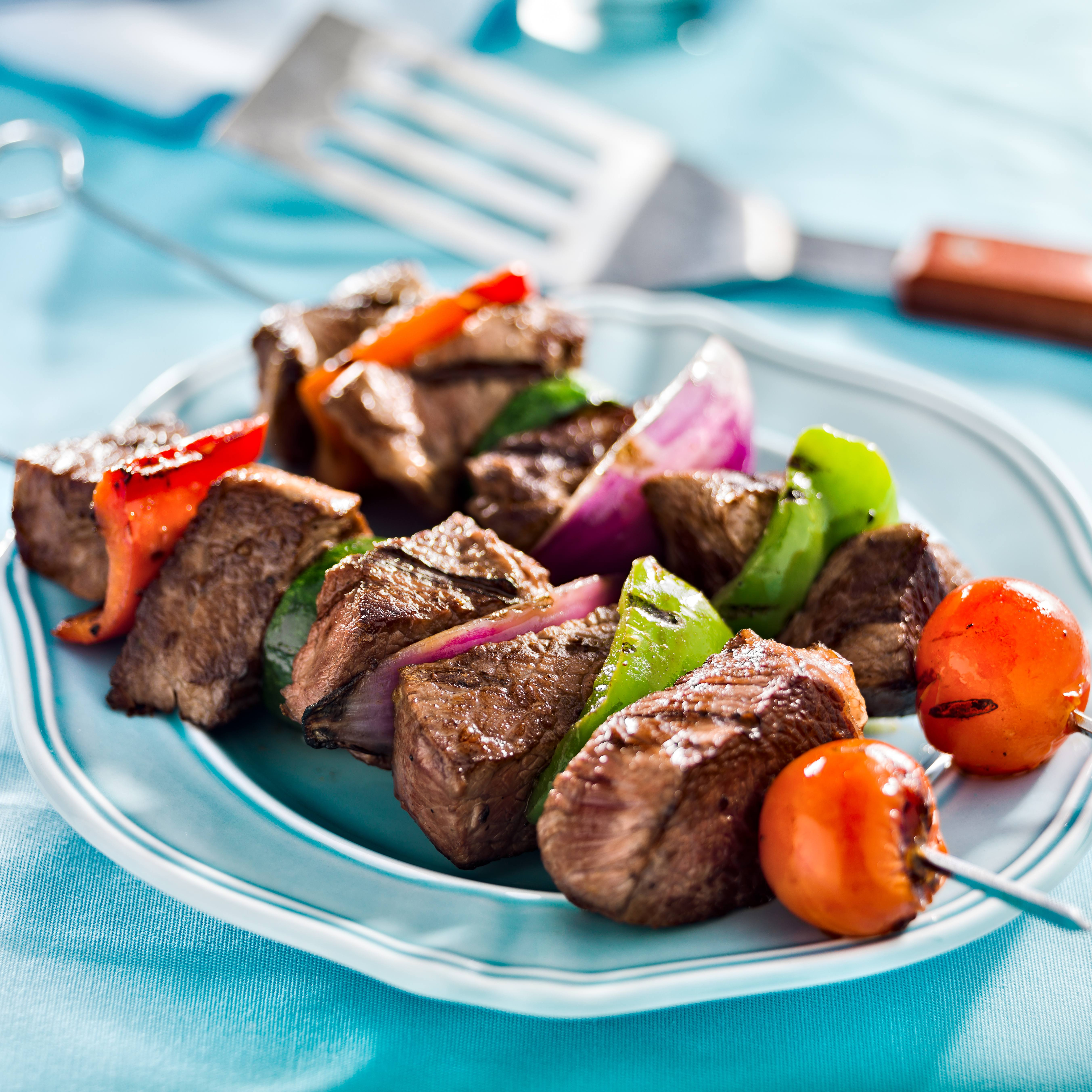 a close-up of a plate of grilled beef and vegetable shish kebabs