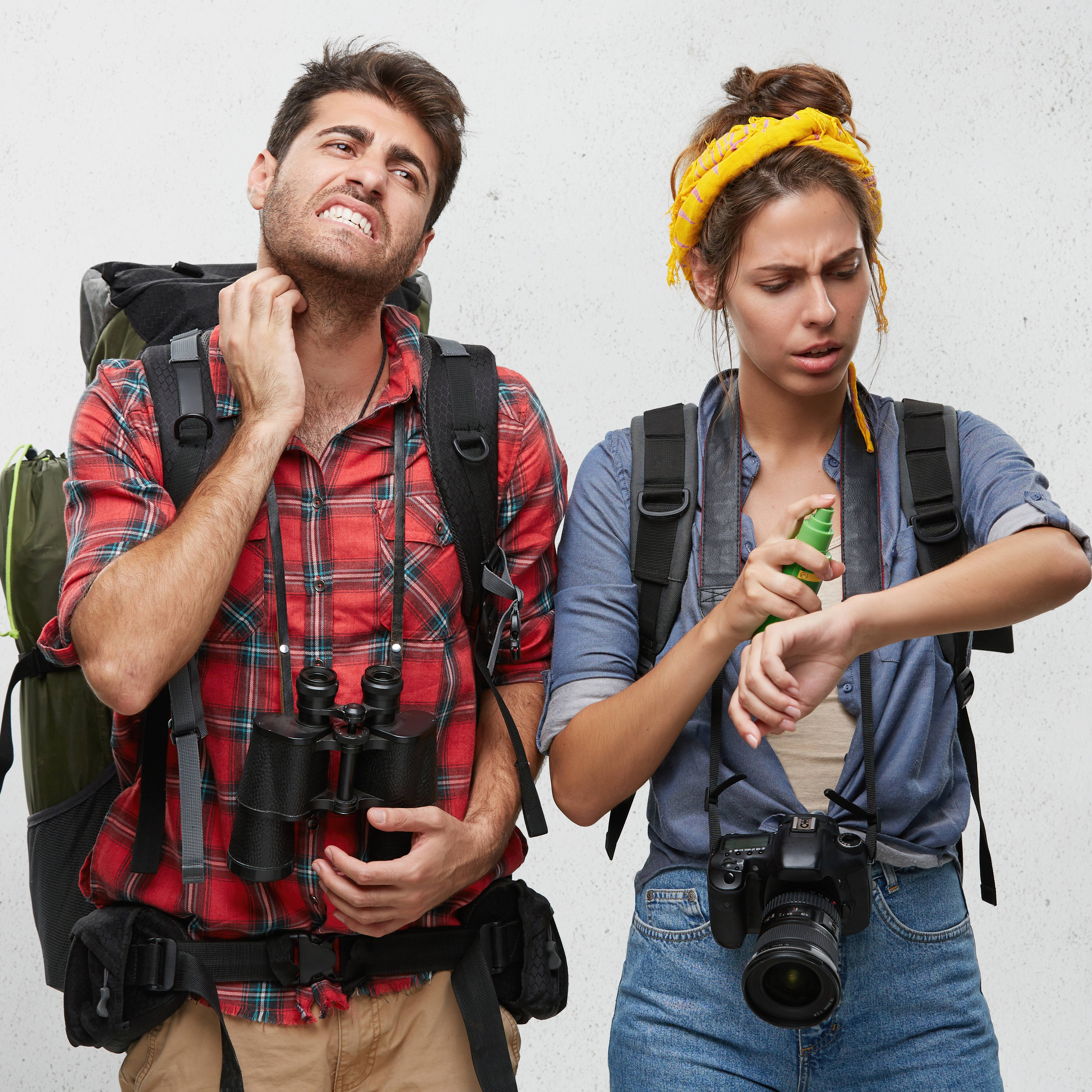 a young couple dressed in hiking or camping clothes, looking distressed, scratching at insect bites