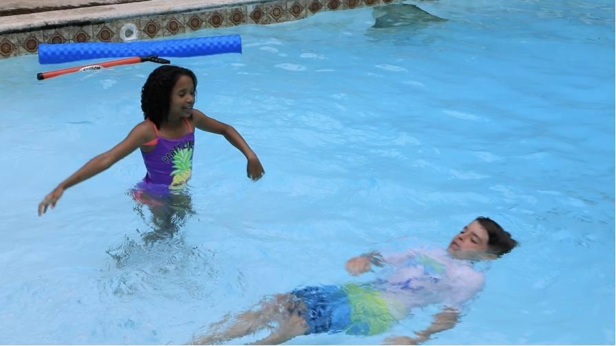 Kids in a pool swimming