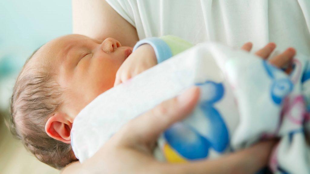 Un recién nacido envuelto en una manta es acunado en brazos