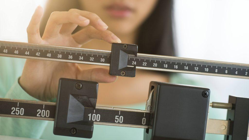 una mujer joven que se pesa y ajusta la balanza