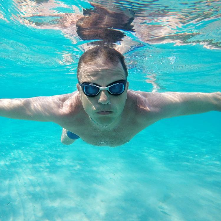 a man wearing water goggles and swimming underwater in a pool
