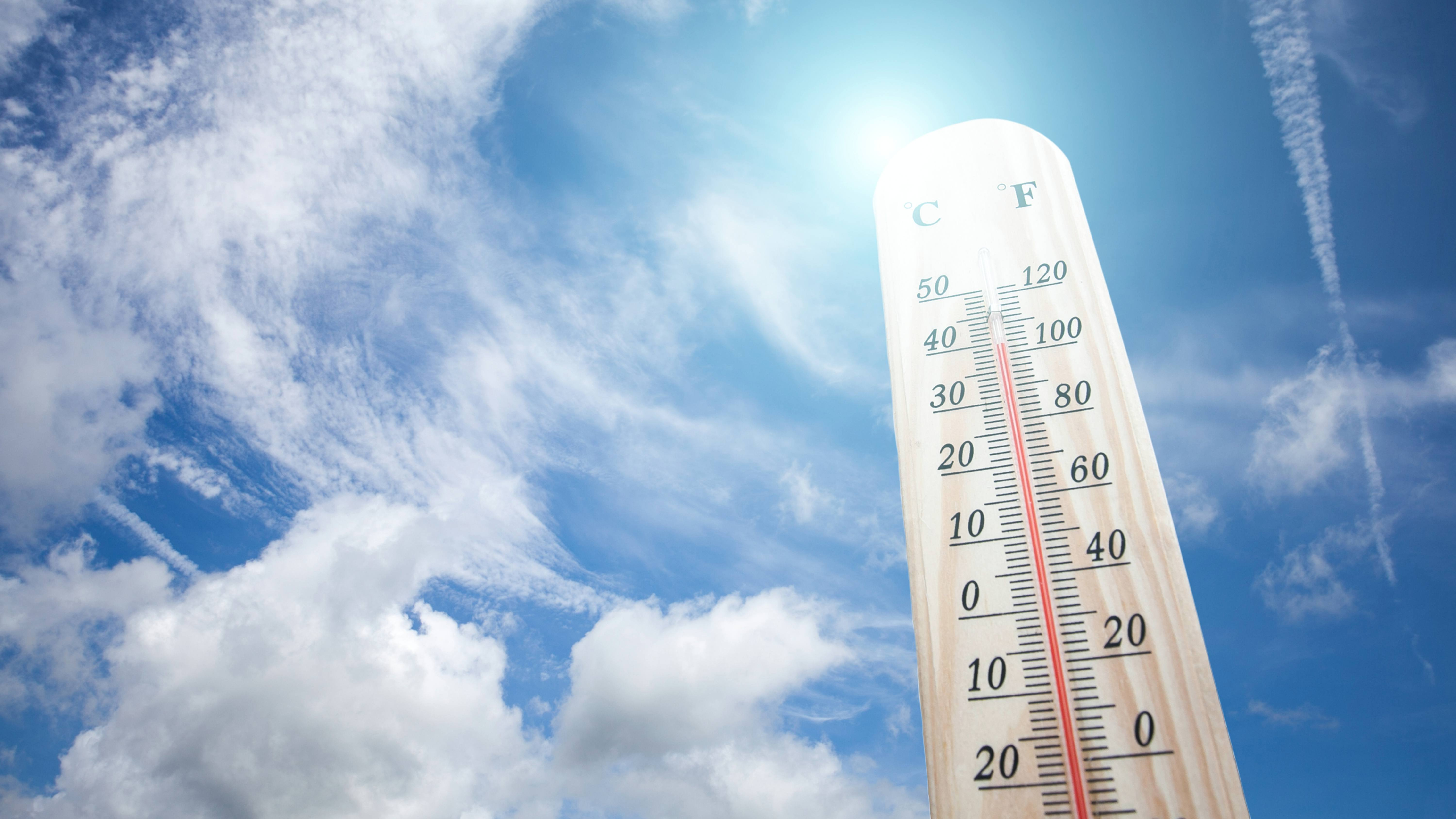 a thermometer on a hot day against a blue sky and sunshine, with high temperature readings, perhaps during a heatwave