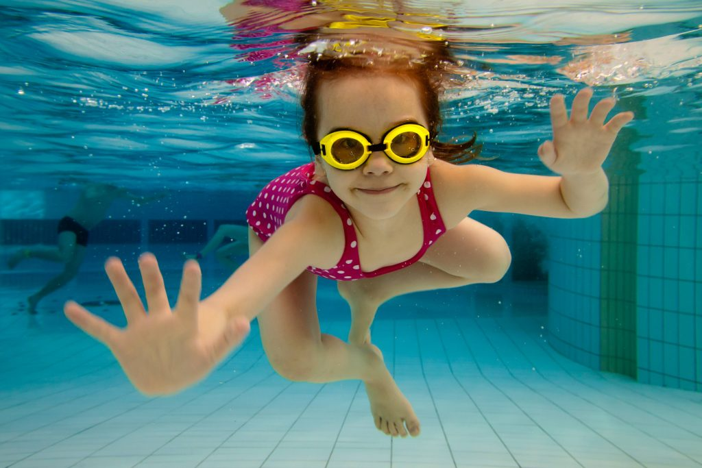 a little girl wearing water goggles and swimming underwater in a pool
