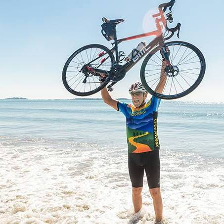 In the Loop patient Chris Edgerton on the beach, at the edge of the ocean, holding his bicycle up in the air
