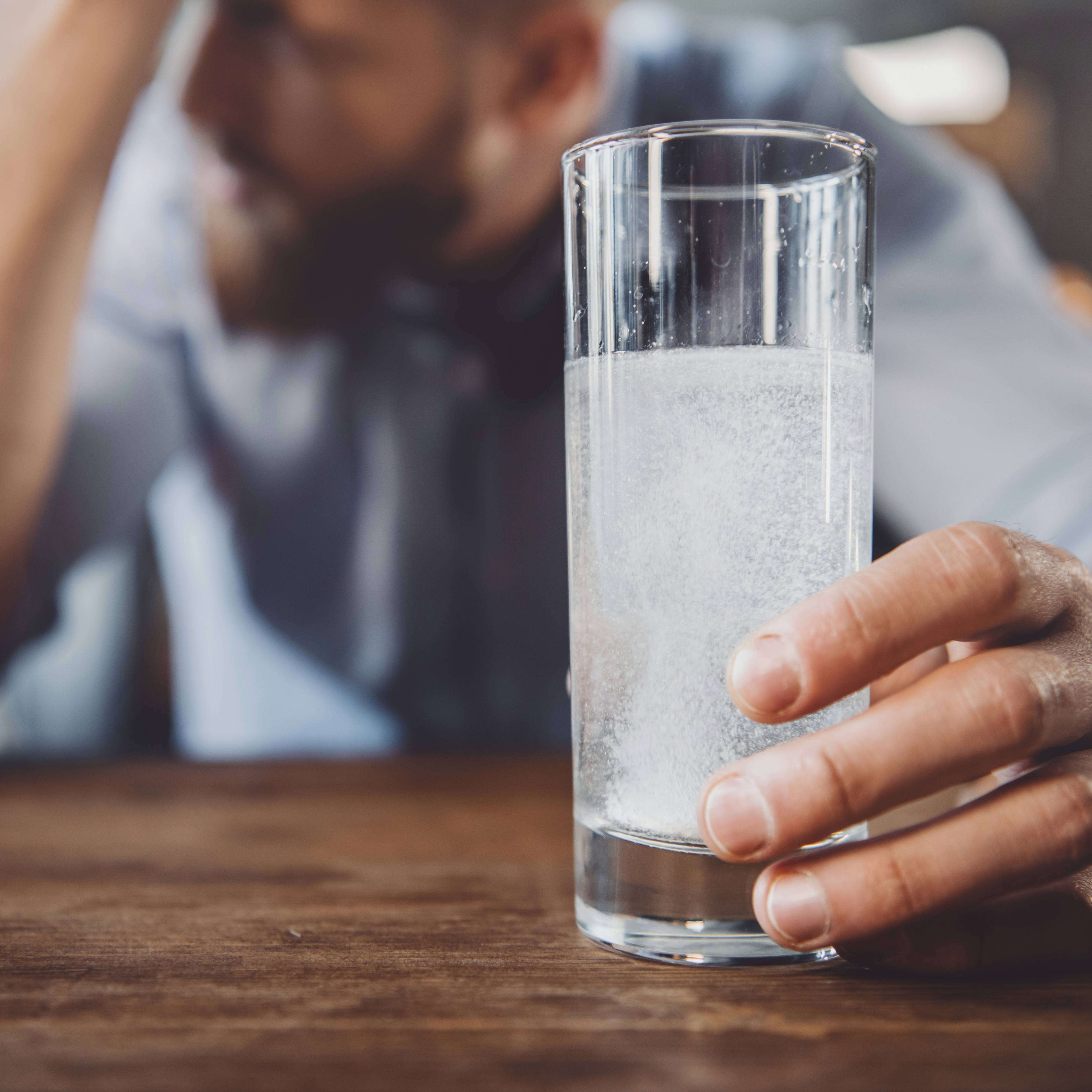 man with hangover with a glass of water with pain reliever