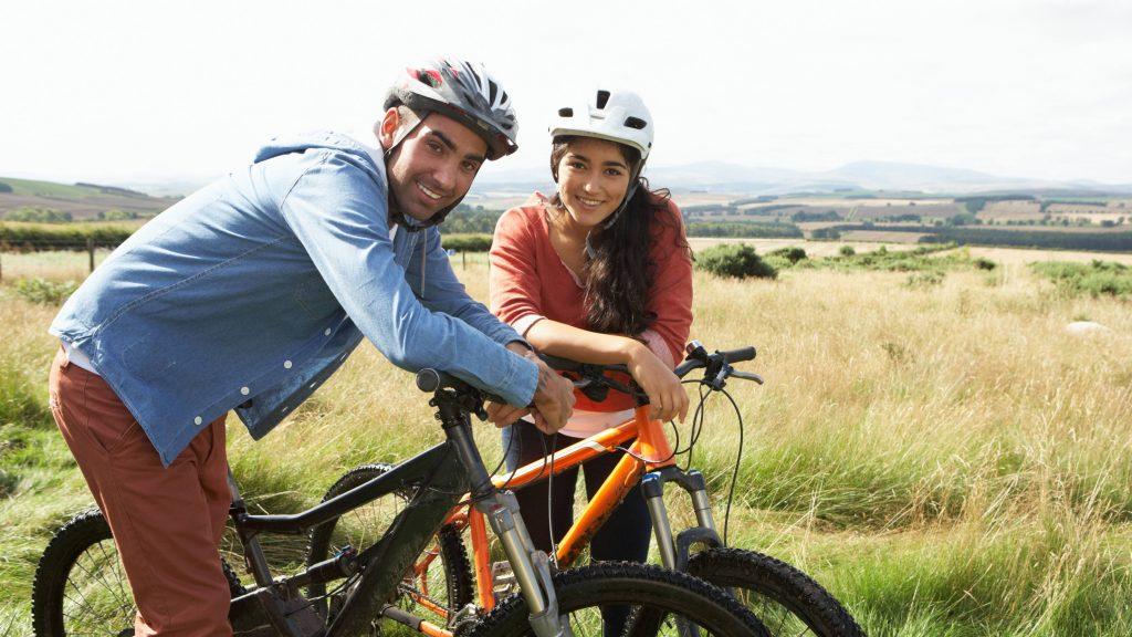 Una pareja joven anda en bicicleta por el campo