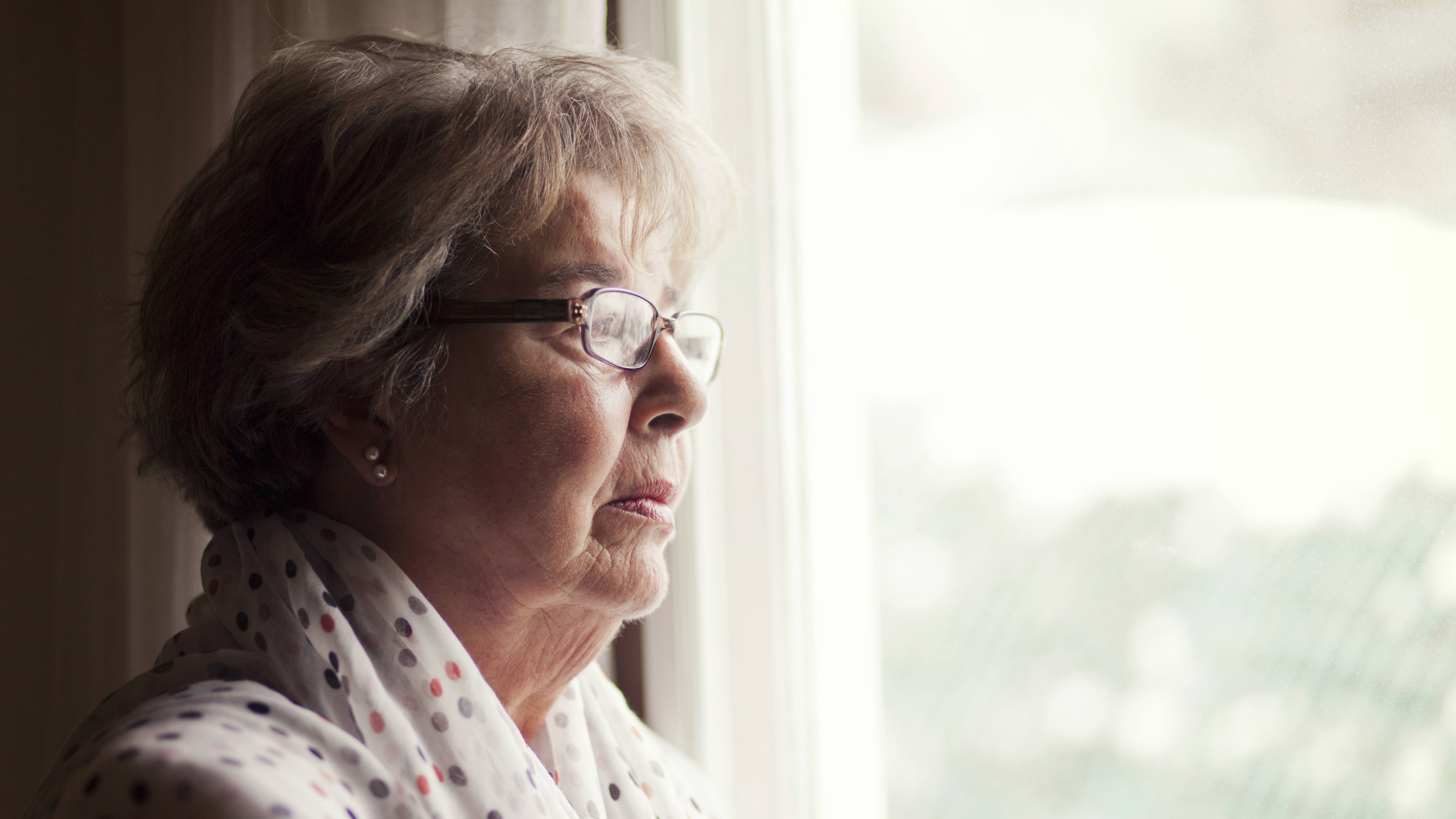 a middle-aged woman wearing glasses and looking out a window, perhaps sad, disappointed or depressed
